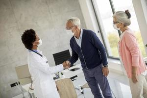 Mature couple greeting doctor with masks on photo