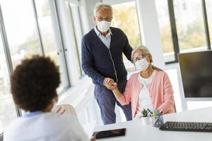 Mature married couple at doctor's office wearing masks photo