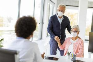 Mature couple speaking to doctor wearing masks photo