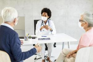 Masked mature couple at doctor's office photo