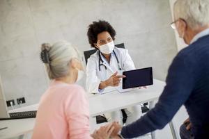 Doctor dando noticias de pareja madura enmascarada foto