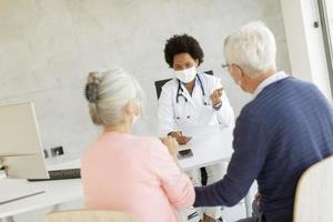 Masked mature couple speaking to doctor photo