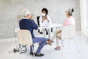 Masked mature couple in doctor's office photo