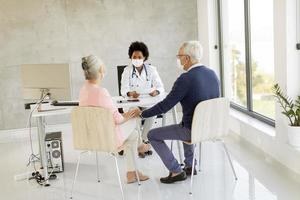 Mature couple receiving news from doctor in masks photo