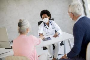 Doctor giving news to masked mature couple photo