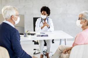 Doctor giving care news to masked mature couple photo