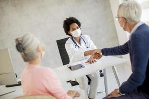 Doctor speaking to masked mature couple photo