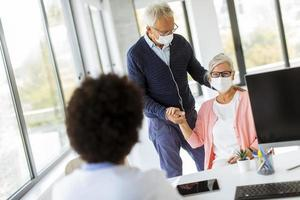 Mature man comforting his wife in doctor's office photo