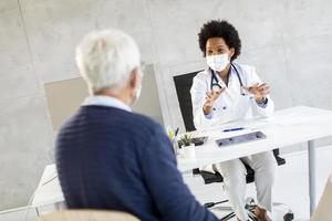 Doctor speaking to mature man in masks photo