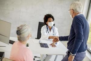Masked mature man shaking doctor's hand photo