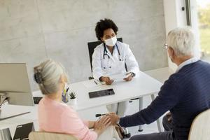 Mature couple receiving news from doctor photo