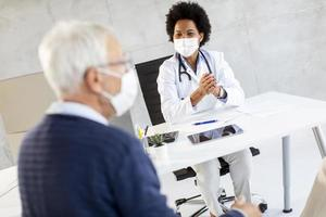 Masked mature man receiving news from doctor photo
