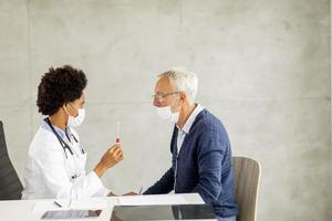 Vista lateral del médico dando a un hombre maduro una prueba de covid-19 foto