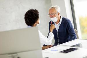 Hombre mayor con máscara facial protectora obteniendo una prueba de covid-19 foto