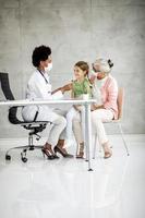 abuela enmascarada con nieta en el consultorio del médico foto