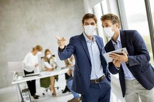 Two masked businessmen talking photo