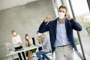 Man in office talking on the phone and wearing a mask photo