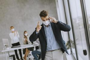 Busy man on phone wearing a mask photo