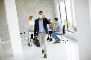 Businessman walking away from meeting and taking on phone with mask on photo