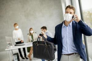 Businessman taking on phone with mask on photo
