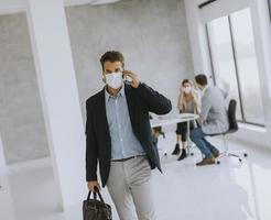 Masked businessman taking on phone and walking in office photo