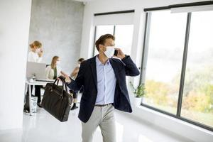 Masked businessman taking on phone with briefcase photo