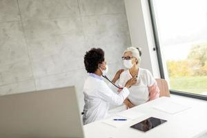 Doctor examining mature woman in mask photo