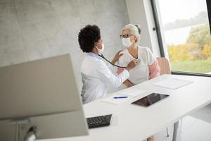 Doctor listening to mature woman's heart photo
