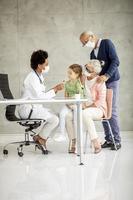 Vista vertical de abuelos y nietos en el consultorio del médico foto