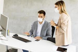 profesionales de negocios que trabajan en el escritorio en máscaras foto