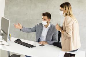 profesionales enmascarados que trabajan en el escritorio foto