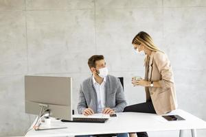 dos profesionales enmascarados trabajando en un escritorio foto