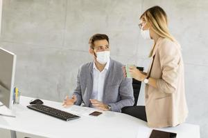 Two masked business people at desk