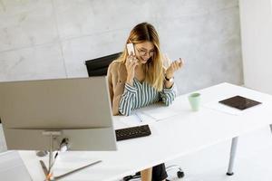 mujer de negocios, por teléfono, en, oficina moderna foto