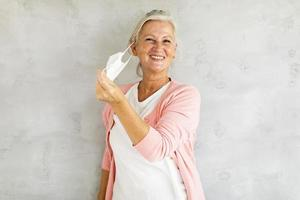 Mature woman taking off mask photo