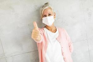 Masked mature woman giving a thumb's up photo