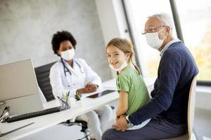 niña con abuelo en el consultorio del médico foto