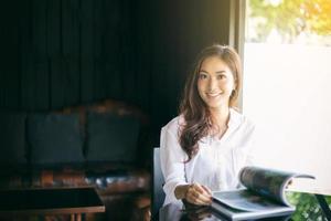 Las mujeres asiáticas sonriendo y leyendo un libro para relajarse en la cafetería. foto