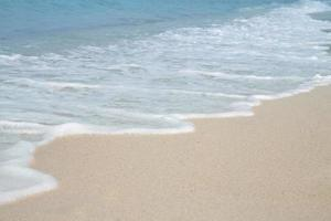 Soft wave and sea bubble of blue sea on sandy beach photo