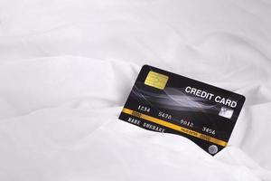 Credit card on white cloth fabric texture background  business shopping online payment concept photo