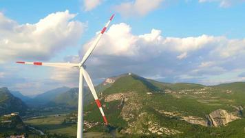 Aerogenerador con nubes y montañas en segundo plano. video
