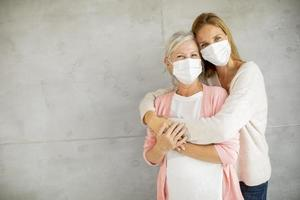 Mature mother and daughter hugging with masks on with copy space photo