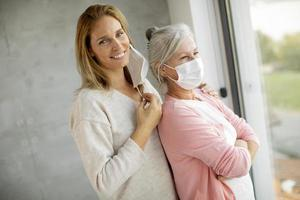 Mature mother and daughter with daughter taking off her mask photo