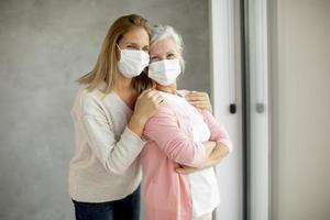Masked mature mother and daughter photo