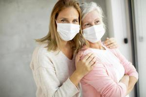 Close-up of masked mature mother and daughter photo