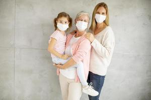 niño, madre y abuela con máscaras. foto