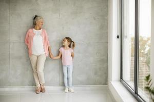 abuela sosteniendo la mano de su nieta cerca de una ventana foto