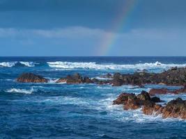 Atlantic waves and a rainbow at the rocky shore of Puerto de la Cruz Tenerife Canary islands photo