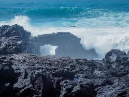 Atlantic waves meeting a rock arch at El Golfo on the volcanic coast of Lanzarote Canary Islands photo