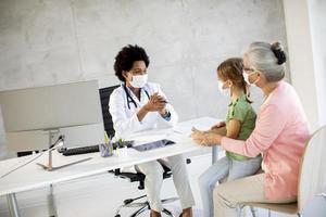 abuela con nieta hablando con el doctor con máscaras foto